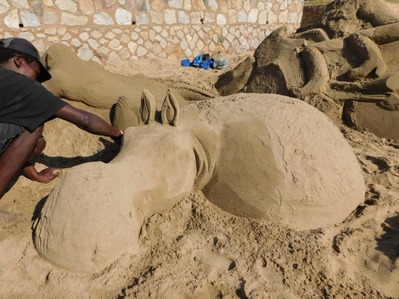 The artist sculpting a sand art hippopotamus on St Michaels on Sea Beach in KwaZulu-Natal